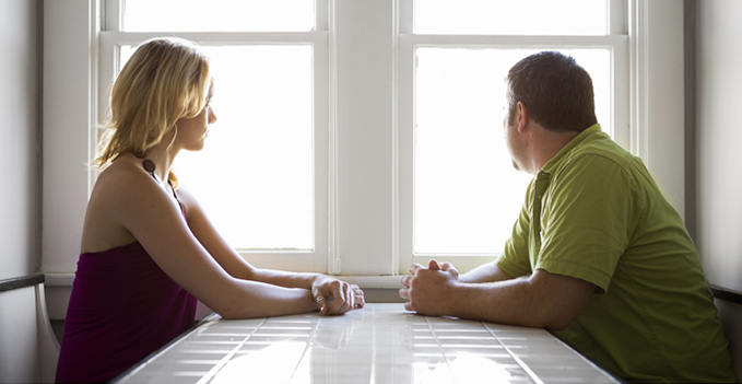 couple meeting and discussing something looking out the window from kitchen table