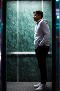 man in an elevator looking at someone